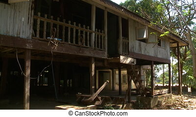 A steady daylight shot of an old and battered all-wood house with an elevated balcony and a gloomy underground crawlspace.