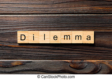 Dilemma word written on wood block. Dilemma text on wooden table for your desing, concept