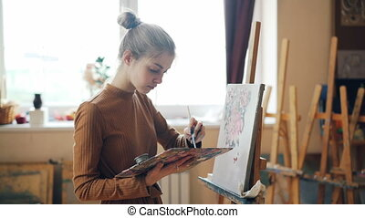 Diligent art school student is mixing bright colors on...