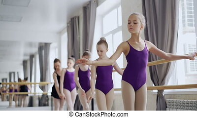 Diligent ballet students are practising arm movements during...