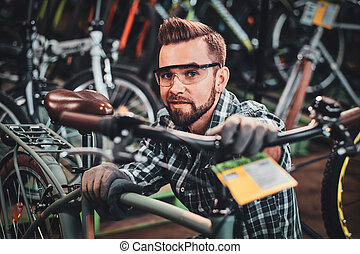 Diligent man is checkin bicycles chain for customer. - Happy...