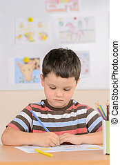 Diligent pupil. Confident schoolboy drawing while sitting in classroom