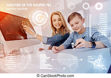 Diligent pupil holding a stylus while his teacher smiling