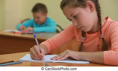 Diligent pupil - Little girl sitting at desk in school and...