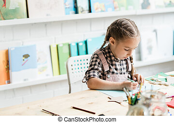 Diligent schoolgirl drawing Christmas picture by desk while working individually