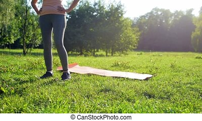 Diligent senior woman doing stretching exercises in the park...