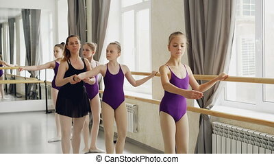 Diligent young ballet-dancers are doing plie and battement...