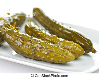 dill pickles on a white dish