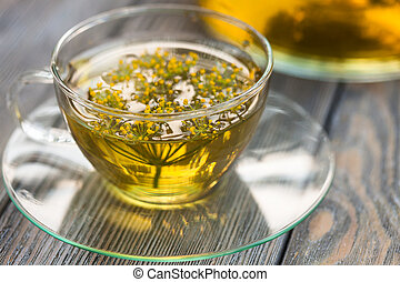 Dill tea - Herbal tea with dill in a glass cup outdoors