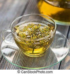 Herbal tea with dill in a glass cup outdoors