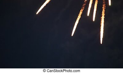 Dim multi-coloured flashes of firework in evening sky