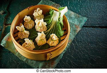 Dim sum dumplings on green leaf in bamboo basket