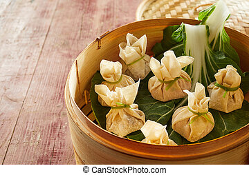 Dim sum dumplings with cabbage in bamboo basket