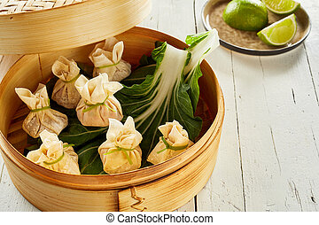 Dim sum on cabbage leaves in bamboo basket