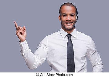 din, text, here., tillitsfull, ung, afrikan bemanna, in, hörlurar med mikrofon, pekande, bort, och, le, medan, stående, mot, grå, bakgrund