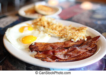 Breakfast of eggs, bacon, and hash brown at a diner.