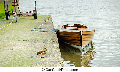 A small wooden dinghy is tethered to a slipway close to the harbour wall.