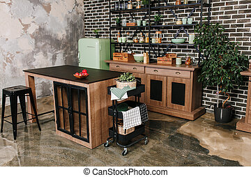 Dining area in industrial style with table, chairs and mint retro fridge. Black vintage brick wall background