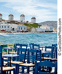 Dining in mykonos at seaside. Behind the famous windmill of ...