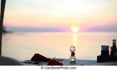 Dining on the beach. Vew of a table at a beach restaurant during sunset by the sea view. 1920x1080