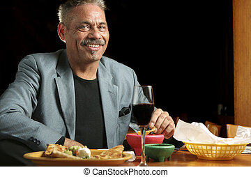 Dining Out Mexican Style - Smiling man dining in a Mexican...