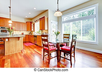 Dining room and kitchen with red cherry wood and large window.