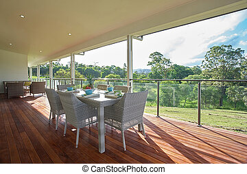 Dining room setting on the patio of modern spacious farm house deck.