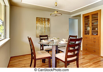 Dining room table with hardwood and green wall.