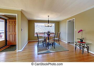 Dining room with flont door and hardwood floor.