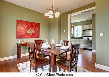 Dining room with green walls and cherry floor.