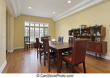 Dining room with tiered ceiling and wood buffet