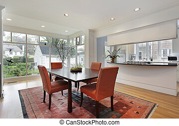 Dining room with wall of windows and orange chairs