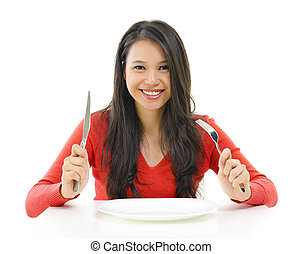 Dining - Mixed race Asian woman holding fork and knife with...