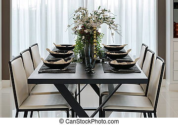 dining table and comfortable chairs in modern home with elegant table setting