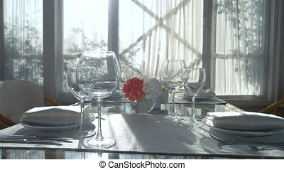 Dining table and sunlight. Plates, napkins and forks. Best...