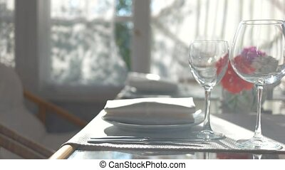 Dining table close up. Empty wineglasses and sunlight. New...