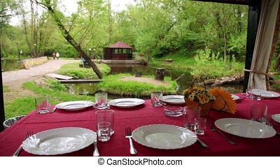 Dining table is set in bower ashore of small pond at among trees at summer