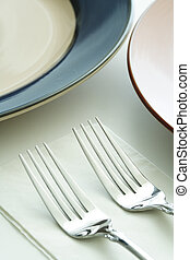 Dining table - A shot of plates and forks on a dining table