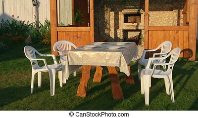 Dining table served on grassy lawn in backyard beside...