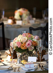 table setting for a wedding or dinner event, very shallow depth of field with the focus on the flowers, blurry background.