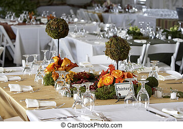 This is a photo of a fancy table set for dinner during a wedding function or party event. Shallow depth of field, with the focus on the table card number thirteen 13