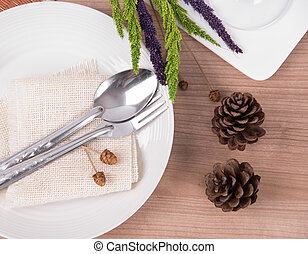 Dining table setting white plate with flower, wineglass, vintage crockery and spoon, fork on wood table background.