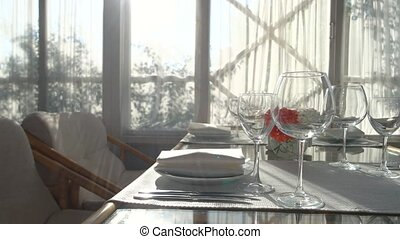 Dining table under sunlight. Empty wineglasses and flower...