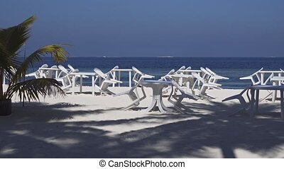 Dining Tables and Chairs on Tropical Beach in the Maldives