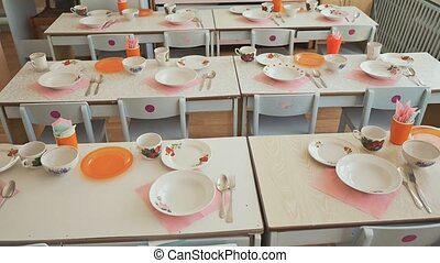 Dining tables with plates, mugs, forks and spoons in the...