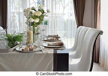 dining wooden table and comfortable chairs in modern home with elegant table setting