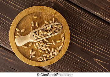 Lot of whole fresh beige dinkel wheat grain with wooden scoop on bamboo plate flatlay on brown wood