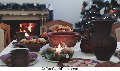 Dinner candle light on Christmas and winter holidays. Set on wooden table with Christmas decorations. Christmas tree and fireplace scene