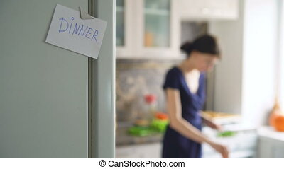 Dinner paper sign on blured background woman cookinf in the kitchen at home