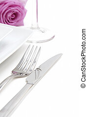 Dinner place setting. A white china plate with fork, knife, glass and pink rose